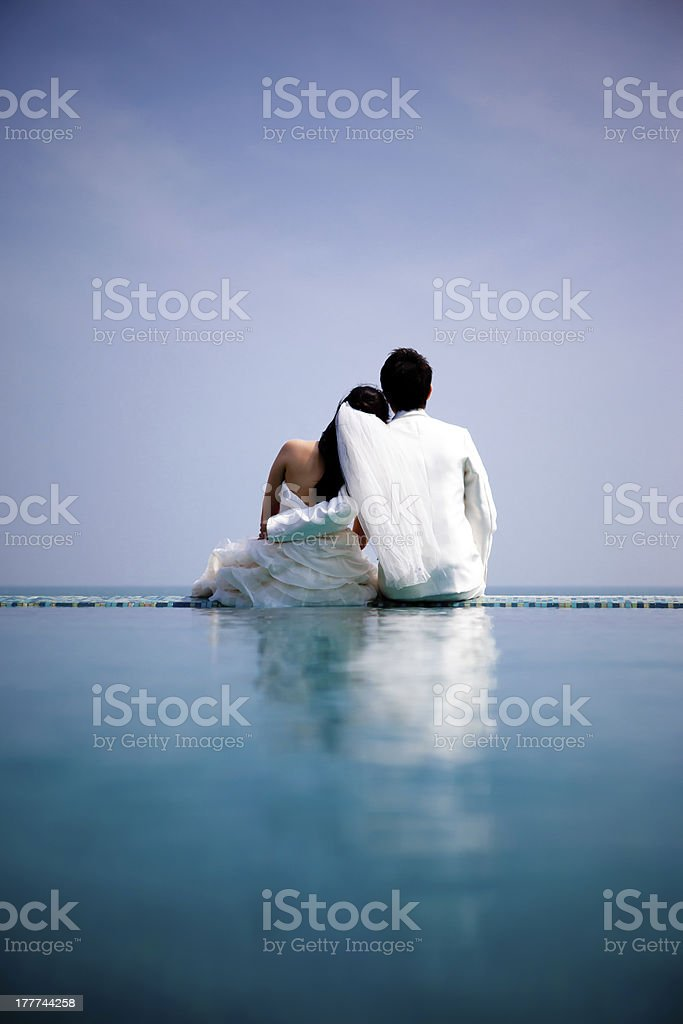 Bride and groom sitting on edge of pool royalty-free stock photo