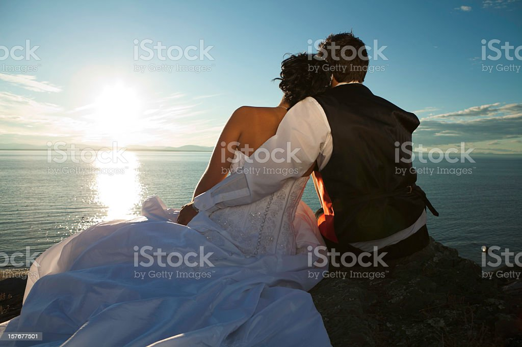 Bride and groom sitting on the ground, enjoying the sunset royalty-free stock photo