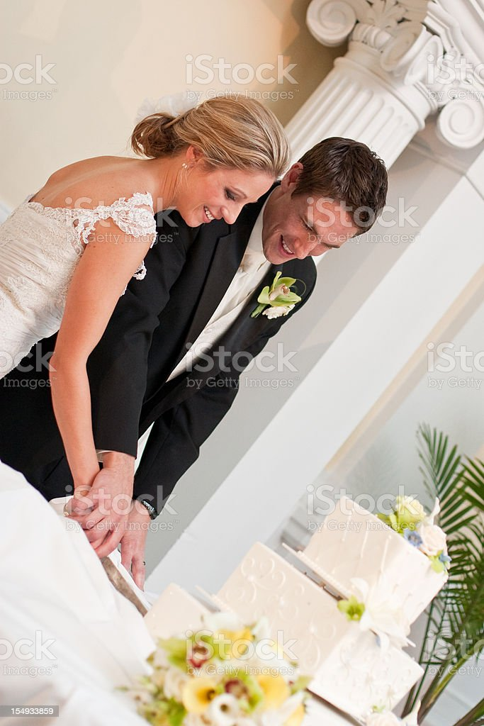 Bride and Groom smiling cutting wedding cake at reception flowers royalty-free stock photo