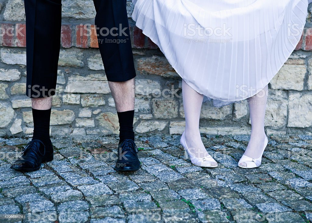 Bride and groom standing agains the wall stock photo