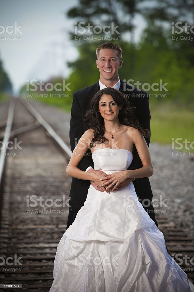Bride and Groom standing on Railroad Tracks royalty-free stock photo