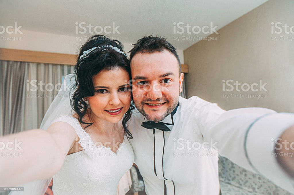 Bride and groom taking selfie pictures with smartphone stock photo