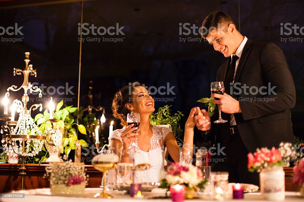 Bride and groom toasting with red wine on wedding ceremony stock photo