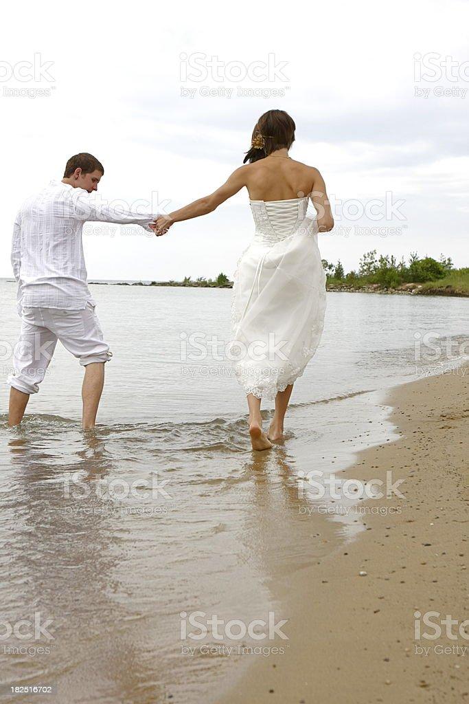 Bride and Groom Walking Along Beach stock photo
