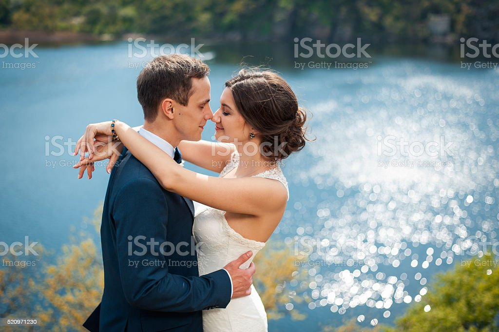 Bride and groom walking at the river stock photo