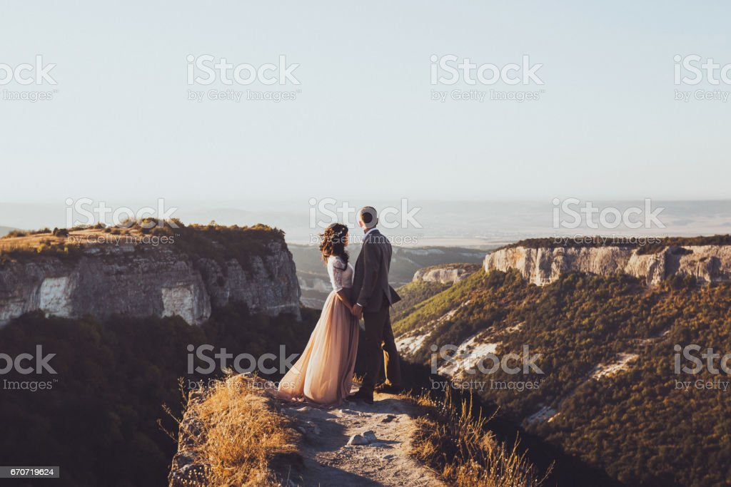 Bride and groom walking in mountains at sunset. Around the stunning scenery with views of the mountains and canyon Mangup stock photo