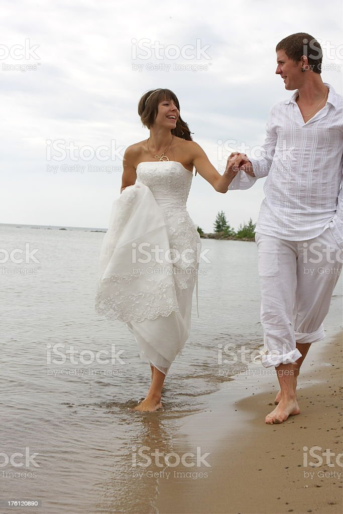 Bride and Groom Walking on the Beach royalty-free stock photo