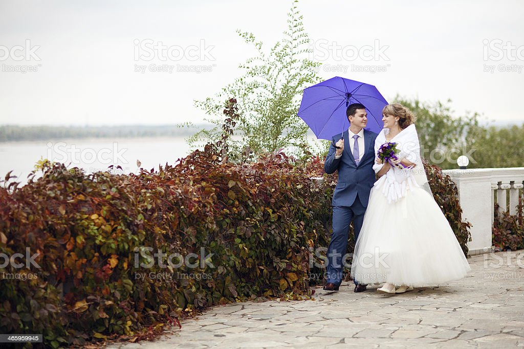 bride and groom walking with umbrella royalty-free stock photo