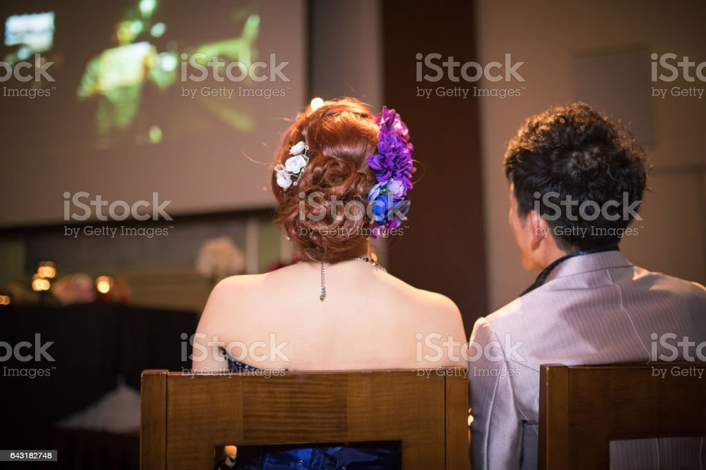 Bride and groom watching video created by friends stock photo