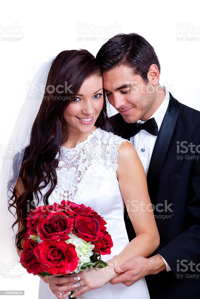 A bride and groom with a red bouquet of flowers royalty-free stock photo