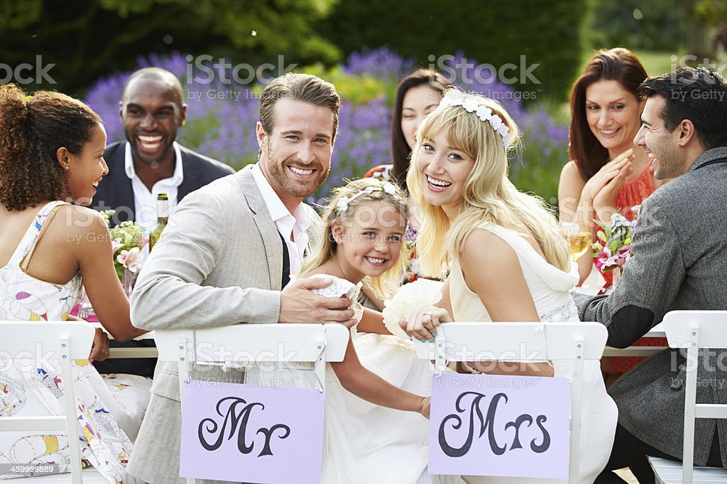 Bride And Groom With Bridesmaid At Wedding Reception stock photo