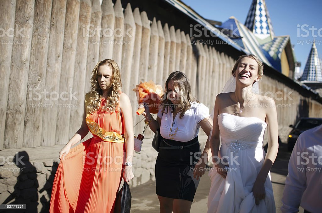 Bride and her bridesmaid walking with friends royalty-free stock photo