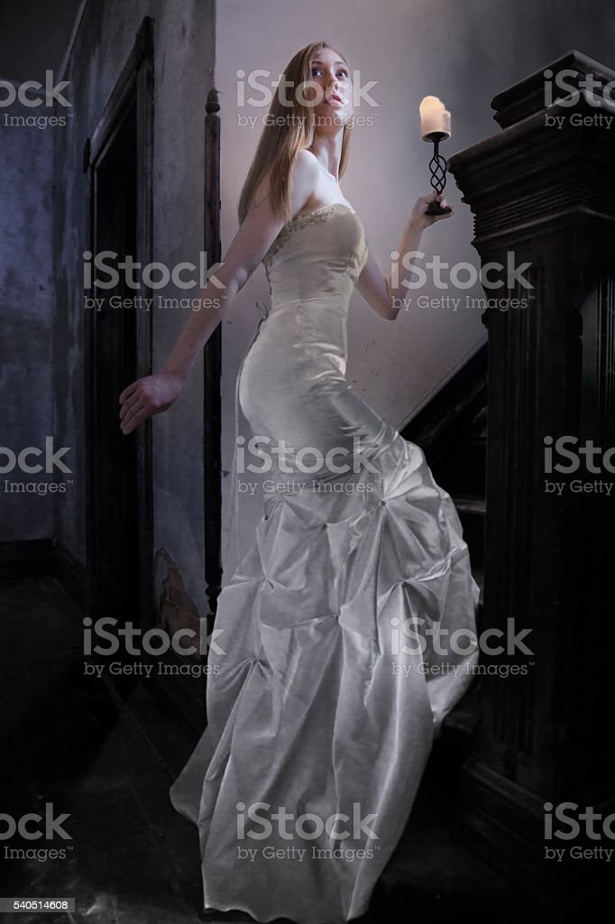 bride ascends stairs in creepy old house stock photo