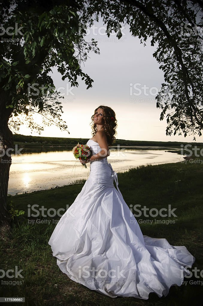 Bride at the riverside under arch of branches, back view royalty-free stock photo