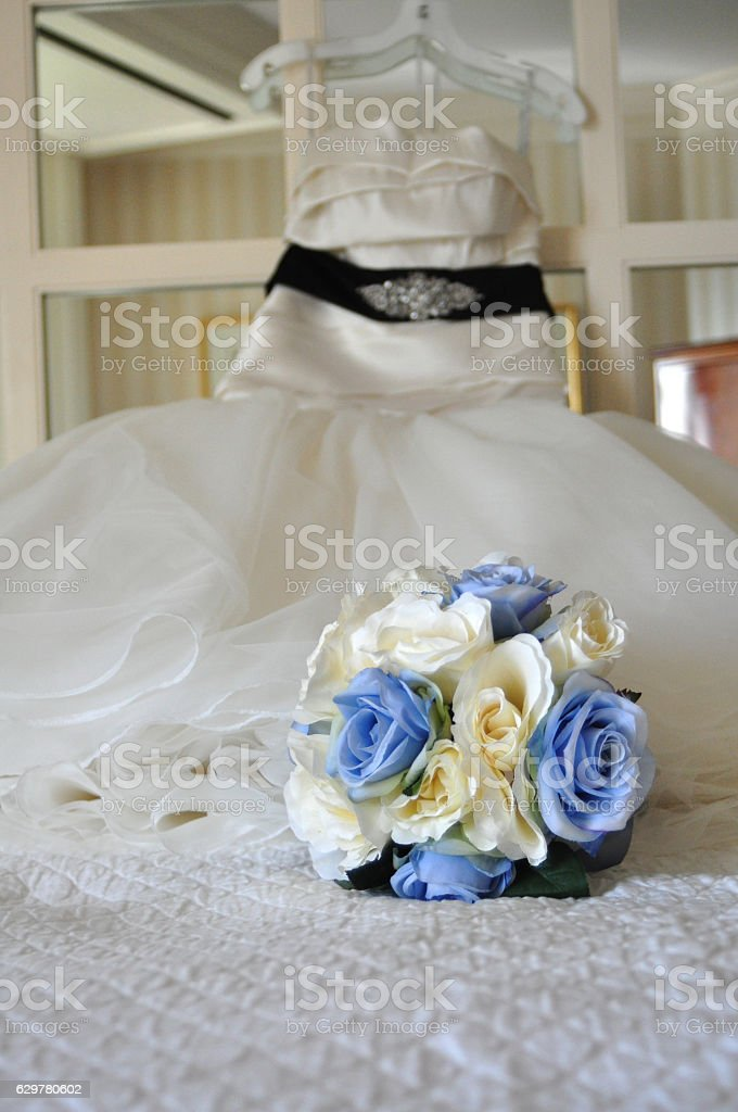 Bride Bouquet on Bed with Wedding Dress Hanging on Mirror stock photo