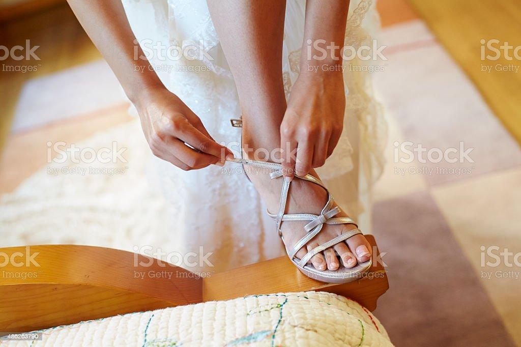 Bride buckling her wedding high heel shoe stock photo