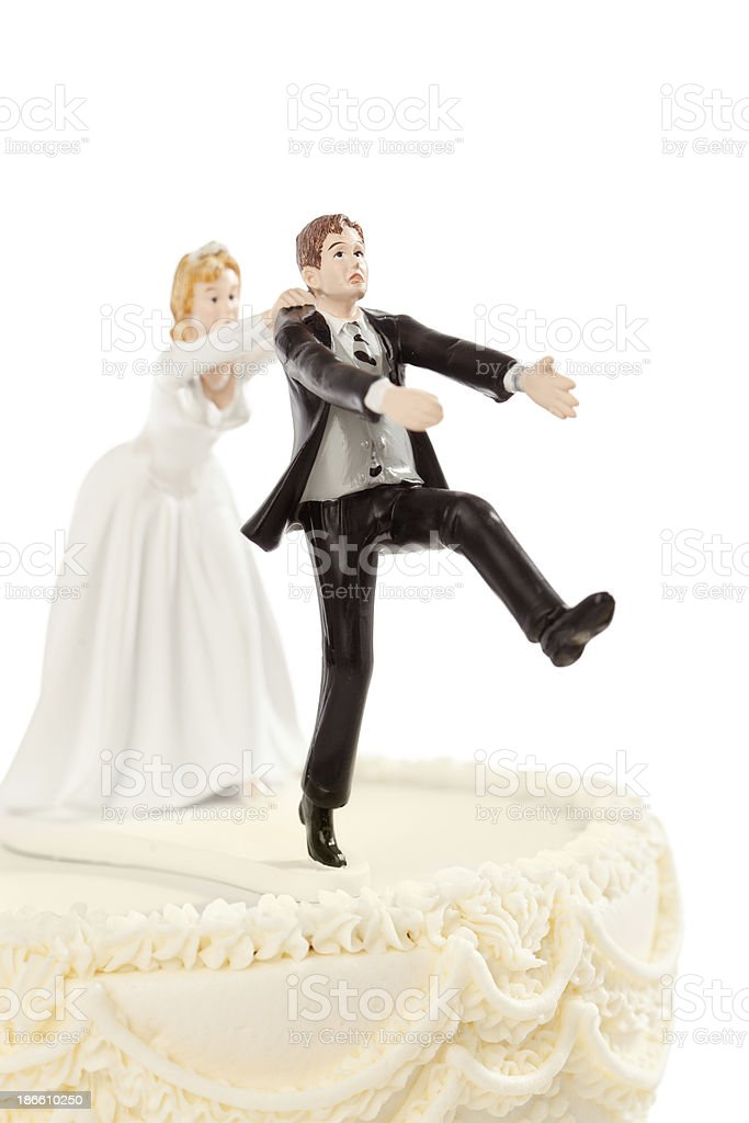 Bride Chasing Groom Humorous Wedding Cake Topper on White stock photo