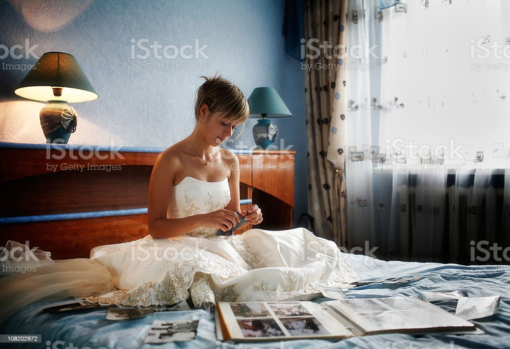 Bride Cries on Bed Surrounded by Photo Albums royalty-free stock photo
