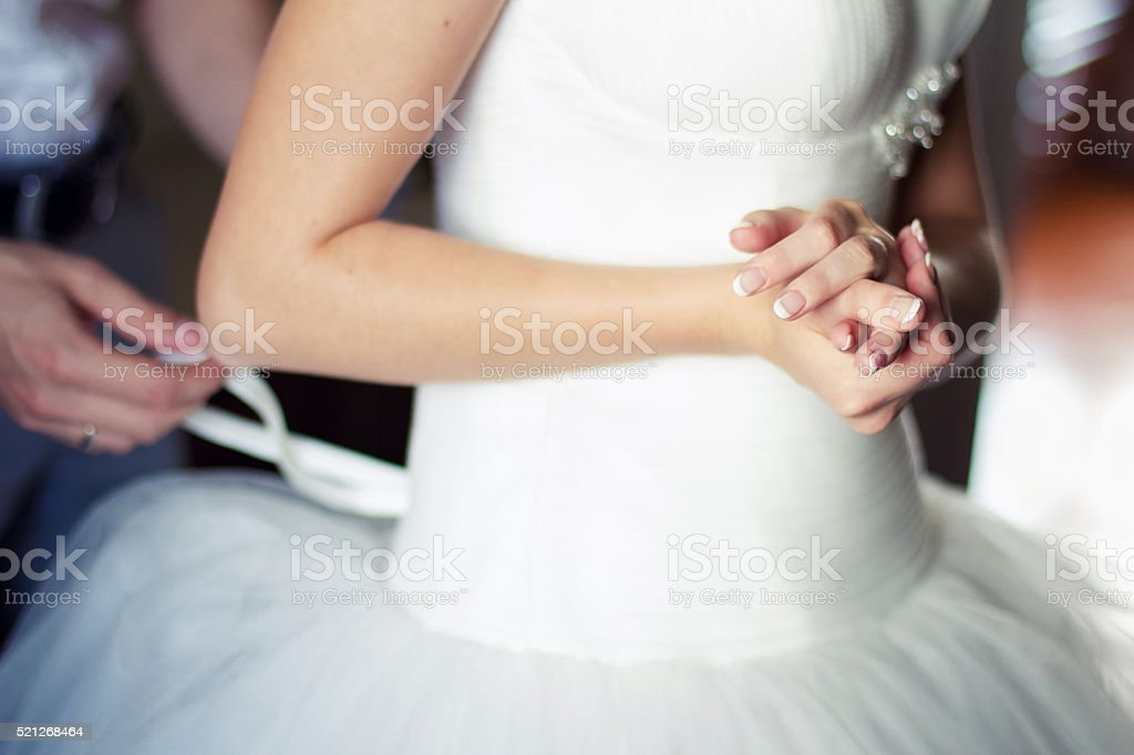 bride dresses a wedding dress in the morning stock photo
