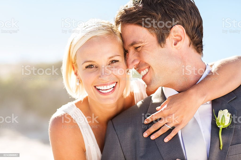 Bride Embracing Groom From Behind On Beach stock photo