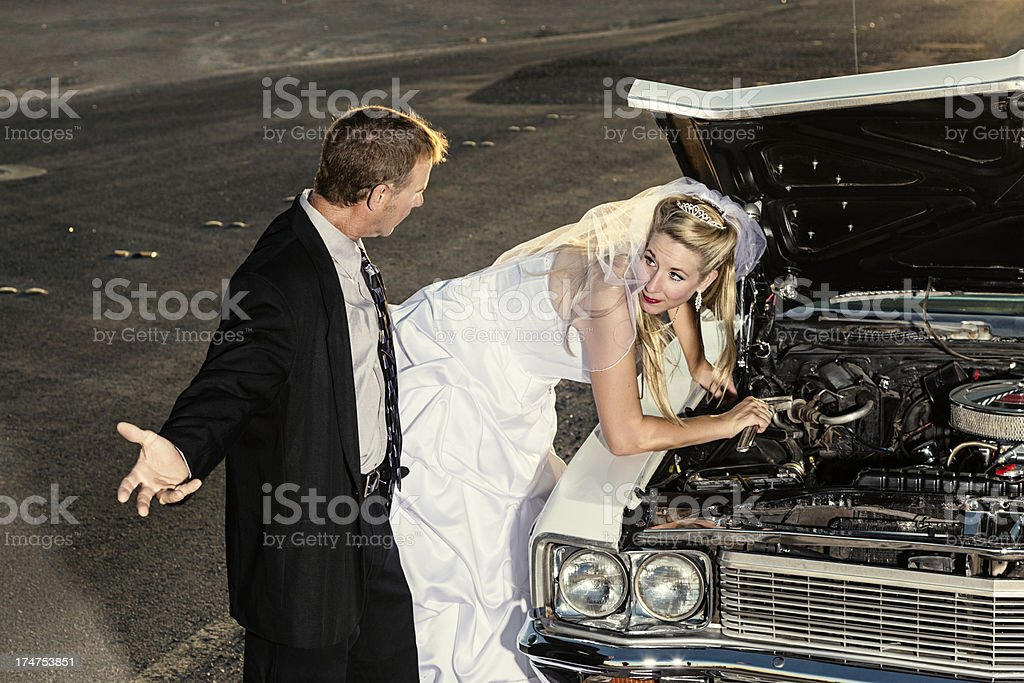 Bride Fixes Car While Angry Groom Looks On royalty-free stock photo