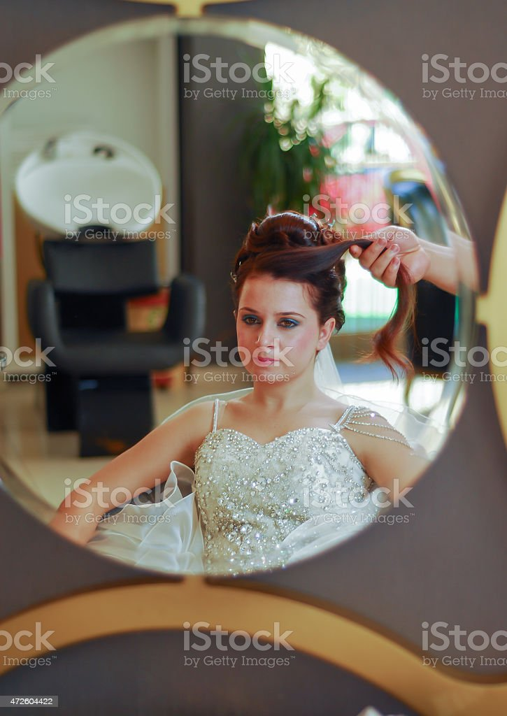 Bride getting her hair done on wedding day stock photo