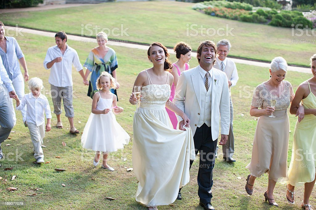 Bride, groom and guests walking across lawn stock photo