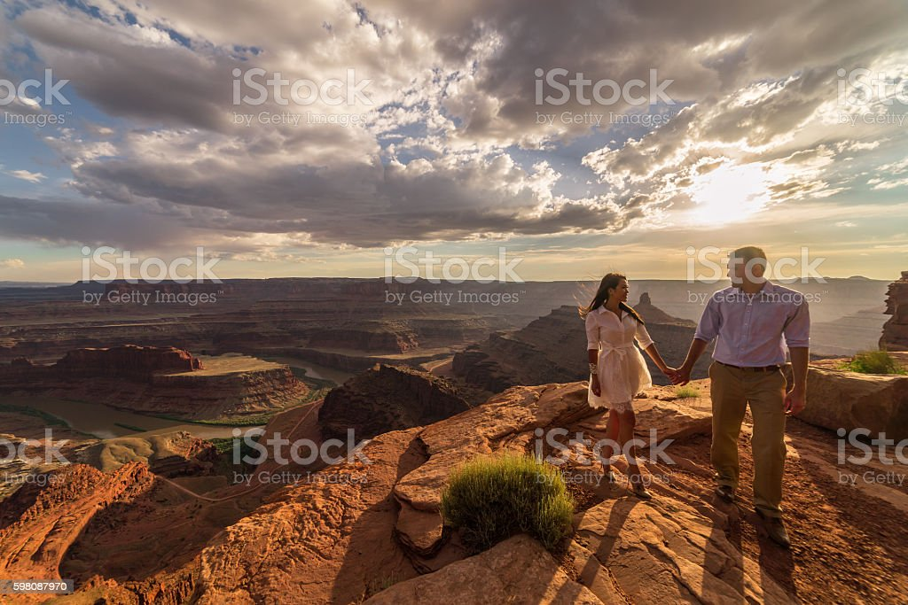 Bride & groom posing over vast canyons.  Utah desert, Moab. stock photo