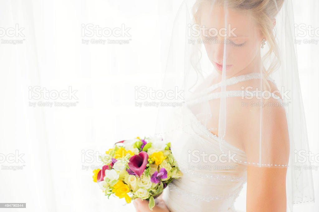 Bride hiding behind veil with flowers in her hands stock photo