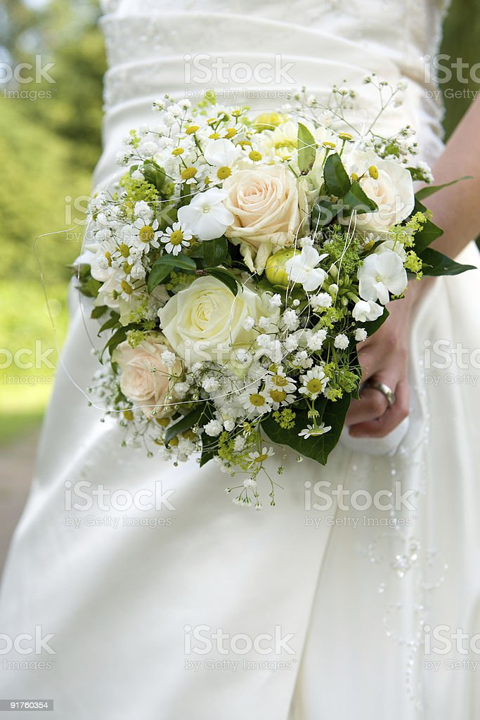 Bride holding a bouquet of beautiful, bright flowers stock photo