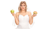 Bride holding an apple and a hamburger