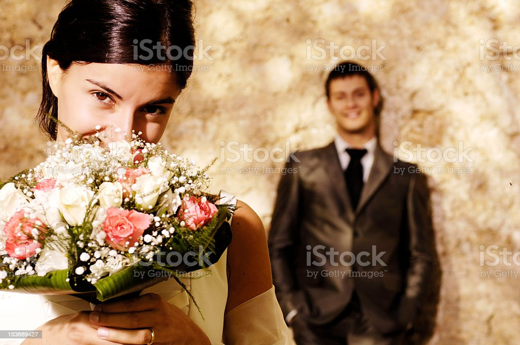 Bride holding flowers in front of her face stock photo