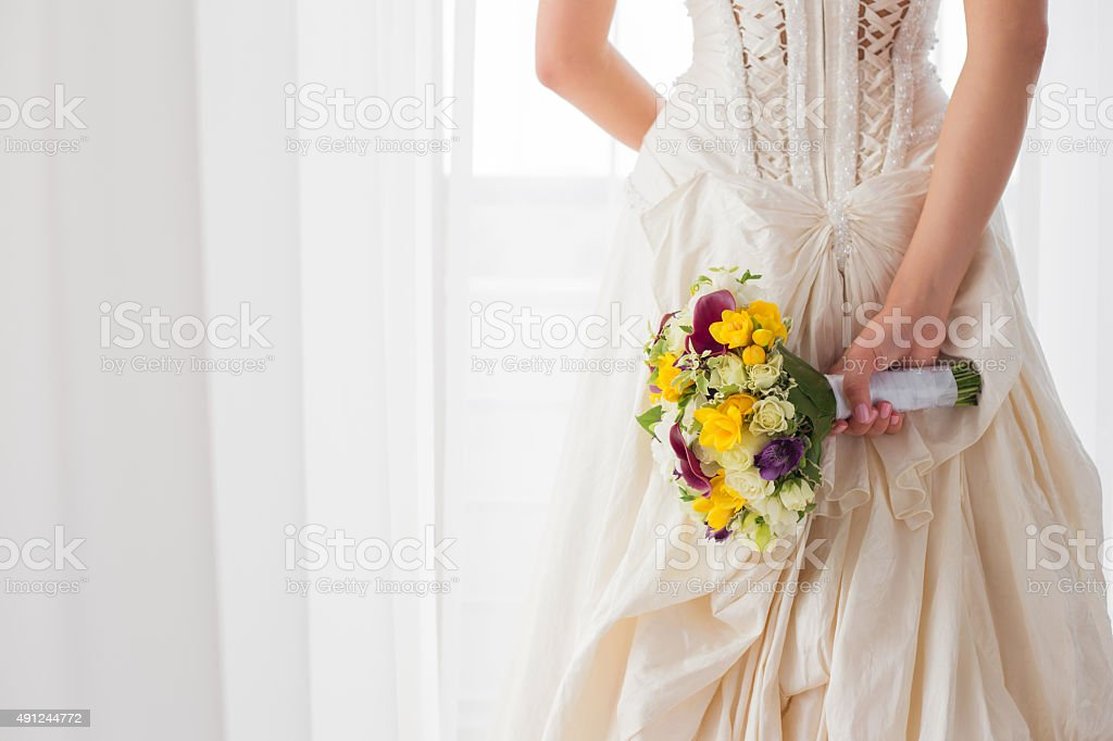 Bride holding her wedding flowers behind her back stock photo