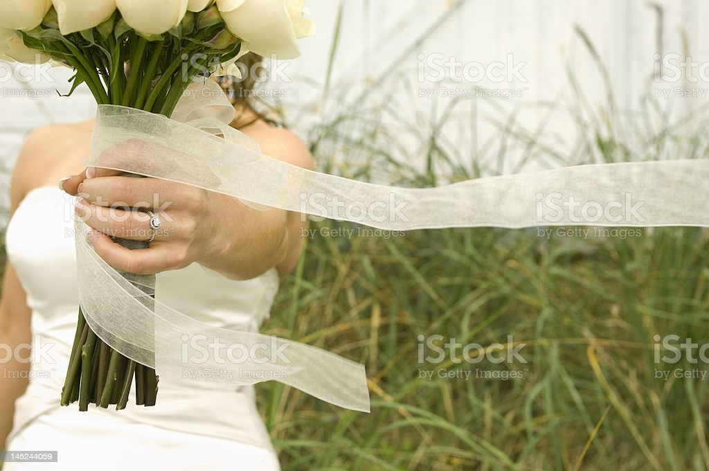Bride holding out her bouquet royalty-free stock photo