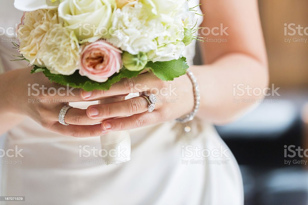 Bride Holding Rose Bouquet with Wedding Ring on Finger stock photo