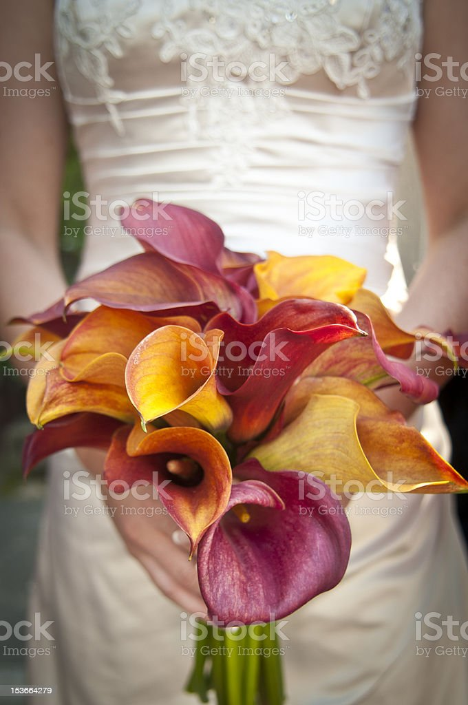 Bride holds bouquet in from of desk stock photo