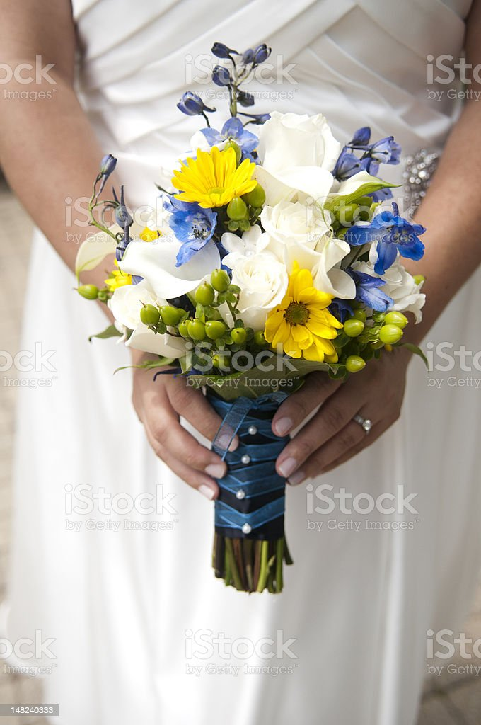 Bride holds bouquet of yellow, blue and white flowers stock photo