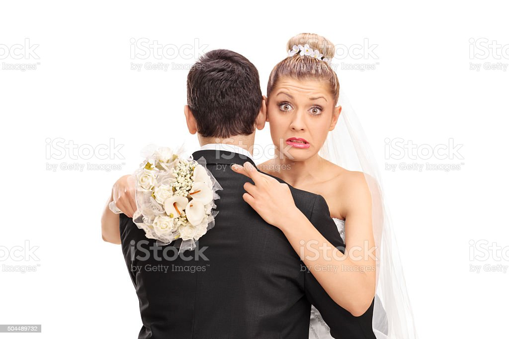 Bride hugging her husband with her fingers crossed stock photo