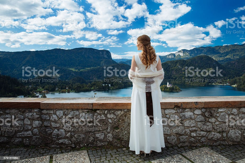 Bride in a castle looking at Lake Bled, Slovenia stock photo