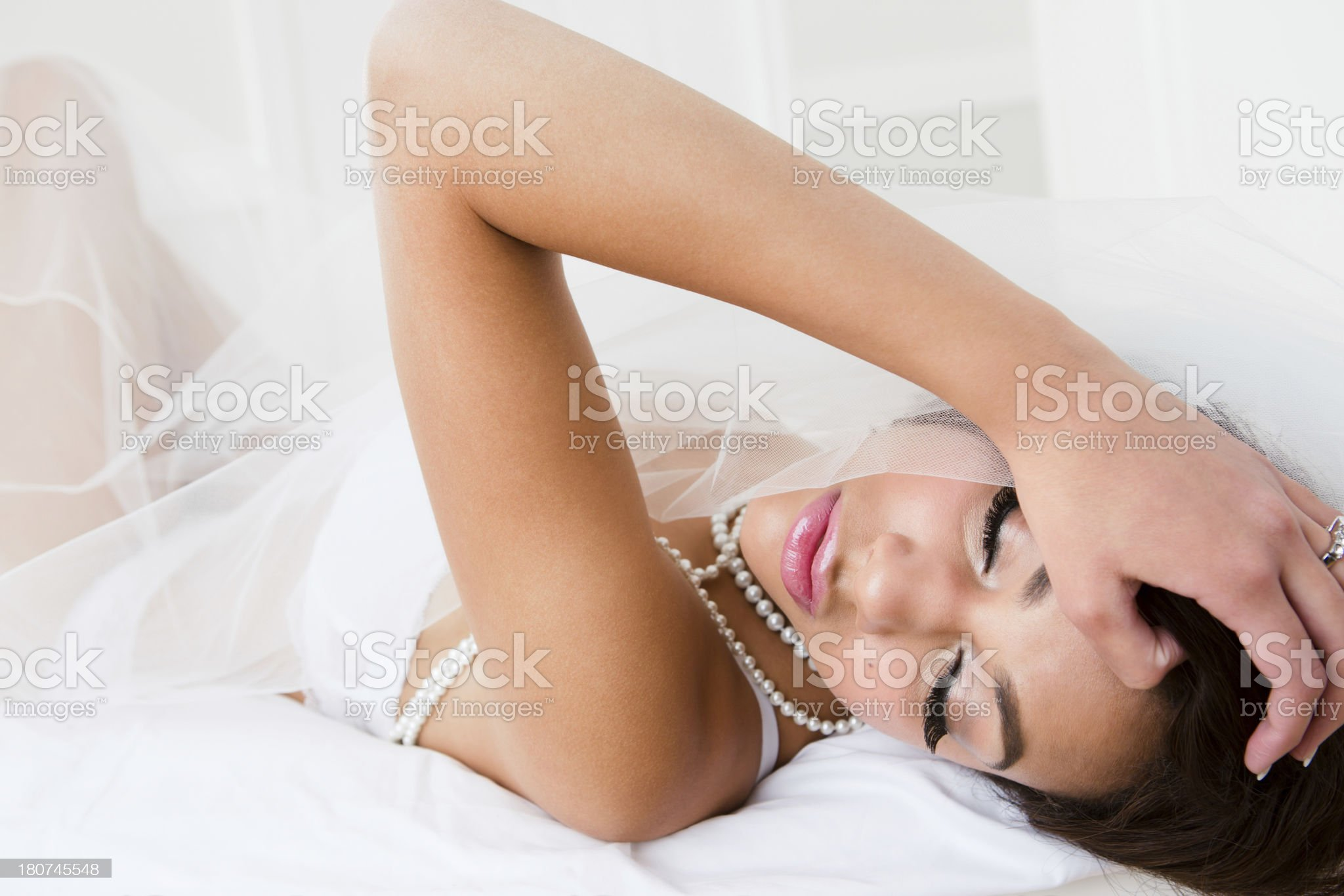 Bride in lingerie laying on bed royalty-free stock photo
