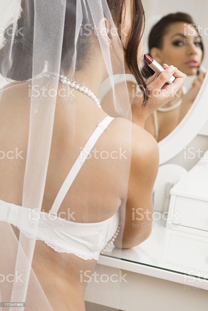 Bride in lingerie putting on lipstick royalty-free stock photo
