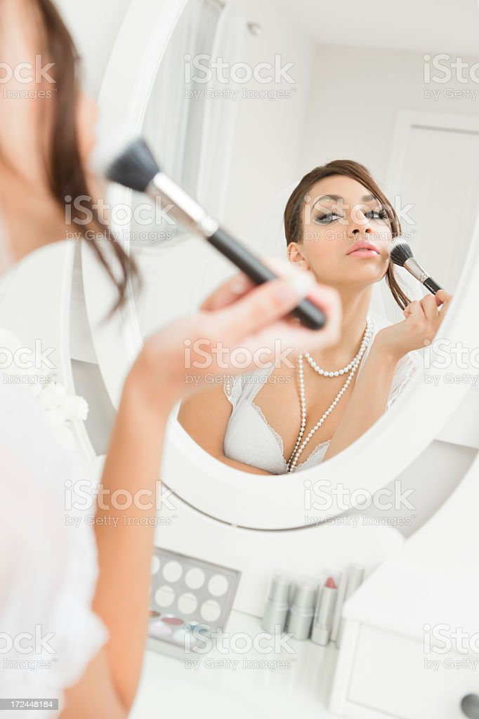 Bride in lingerie putting on make-up royalty-free stock photo