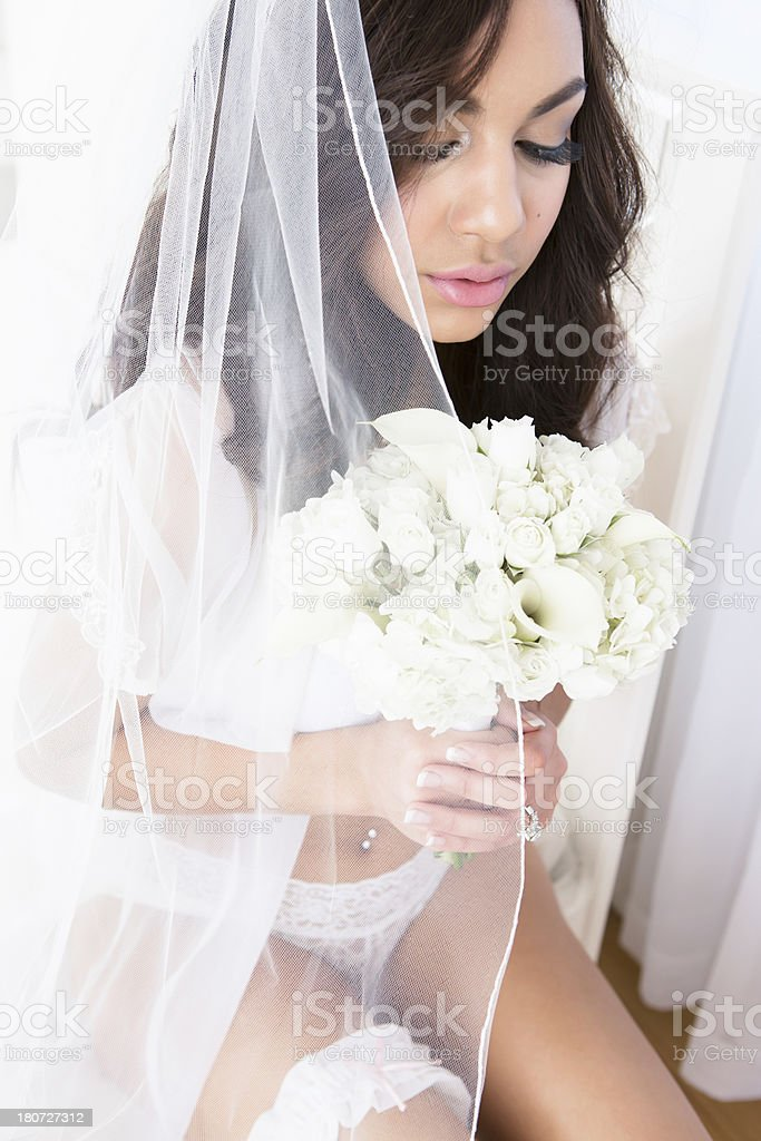 Bride in lingerie sitting on bed royalty-free stock photo