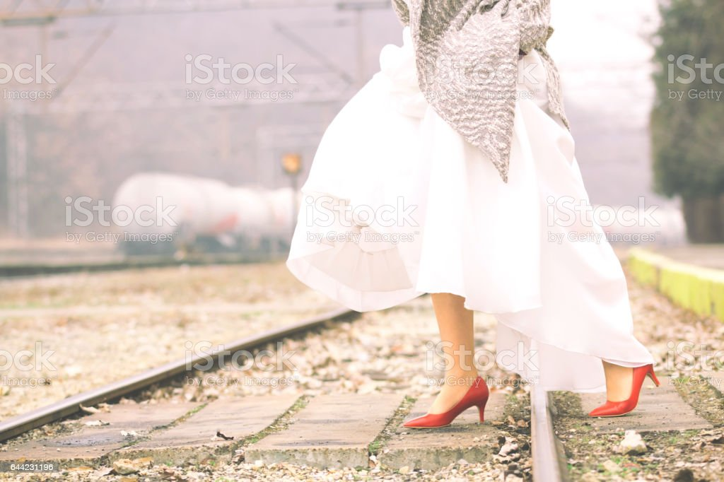 Bride in red shoes walking on a train station. stock photo