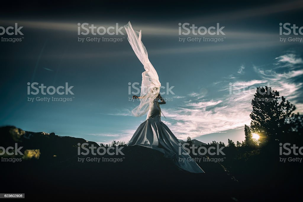 Bride in the mountains with a whipping veil in wind stock photo