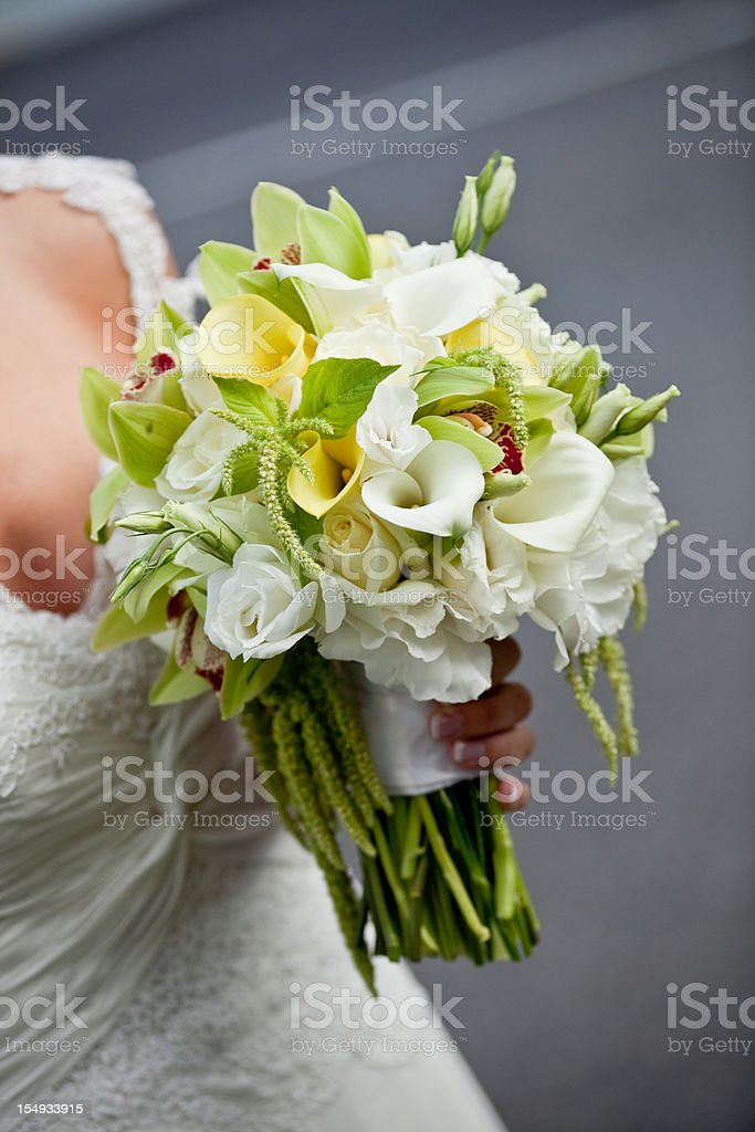 Bride in wedding dress holding white rose floral bouquet royalty-free stock photo