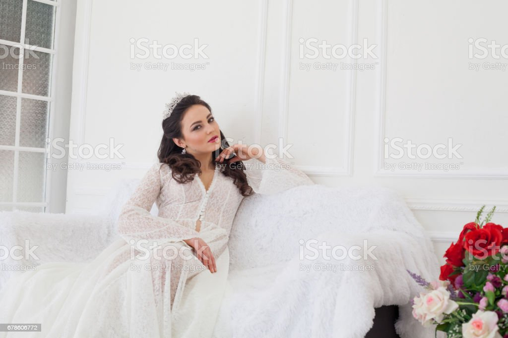 bride in wedding dress sitting on a couch stock photo