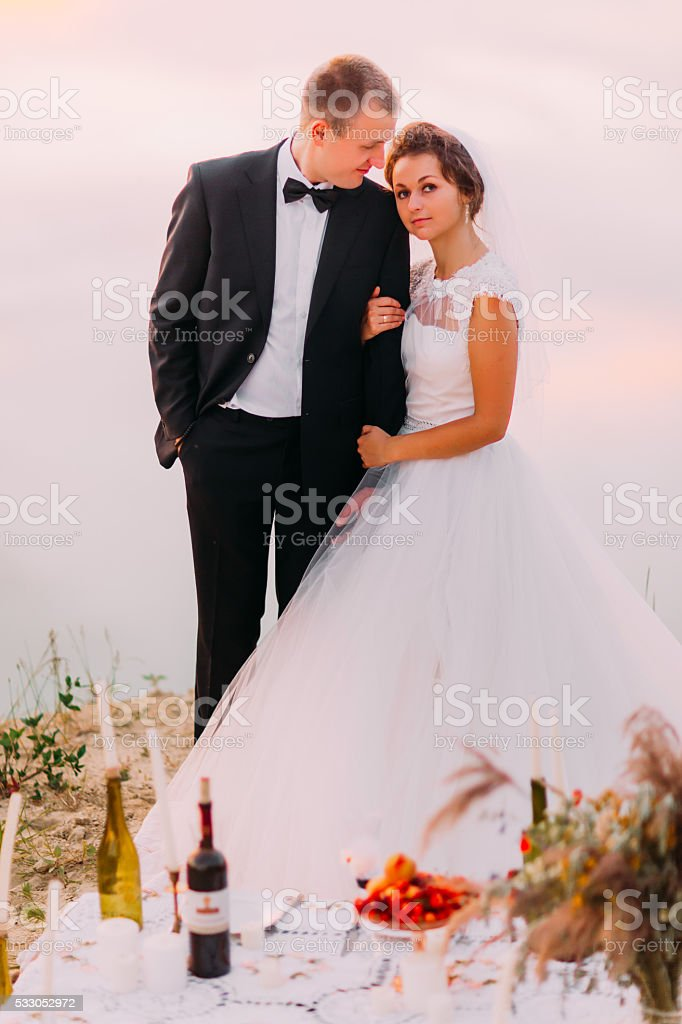 Bride in white veil and groom wearing black suit embracing stock photo