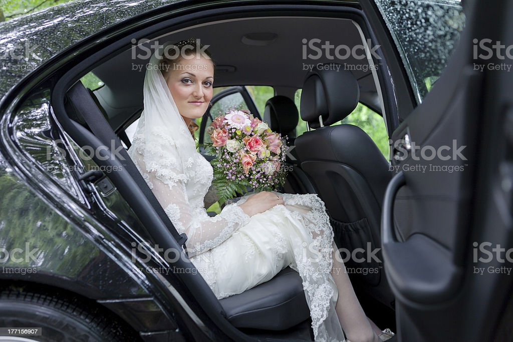 Bride in white wedding dress holding colourful bouquet in black car royalty-free stock photo