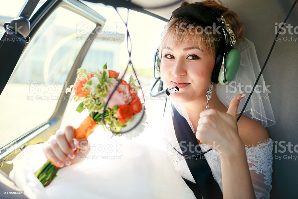 Bride inside helicopter preparing to fly, in headset, thumbs up stock photo